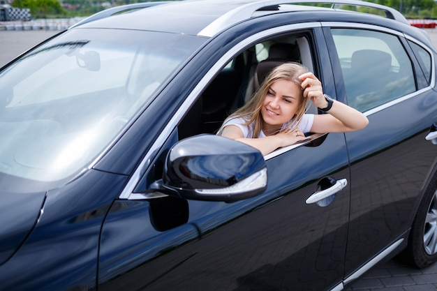 Young beautiful woman with long hair sits in a black car at a parking lot. pretty girl in casual clothes. car trip