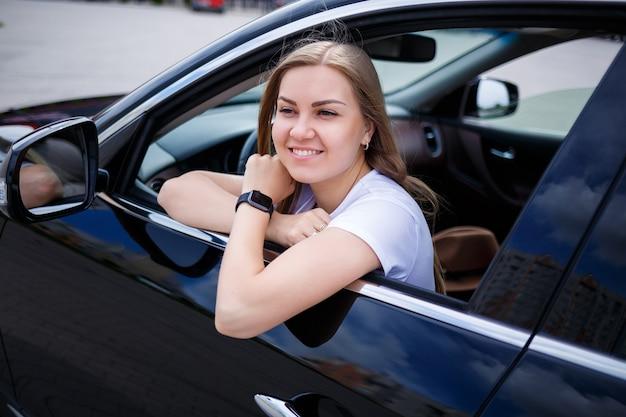 駐車場の黒い車に長い髪の若い美しい女性が座っています。カジュアルな服装の可愛い女の子。車の旅