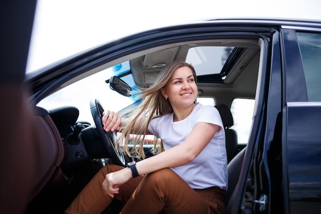 긴 머리를 가진 젊고 아름다운 여성이 주차장에 있는 검은 차에 앉아 있습니다. 캐주얼 옷에 예쁜 여자입니다. 자동차 여행