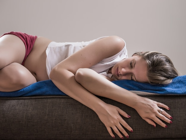 Young beautiful woman with long hair sleeping curl up on the brown bed with stomach ache because menstrual pain soft focus background. young sick woman with hands holding pressing her crotch lower abdomen. medical or gynecological problems, healthcare concept