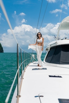 Young beautiful woman with long hair standing on the bow of the yacht