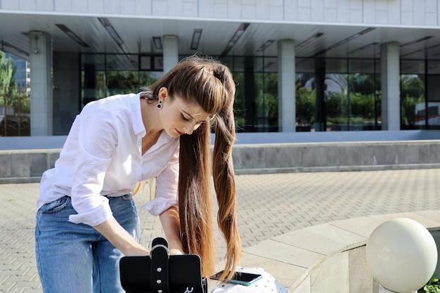 긴 머리를 가진 젊은 아름다운 여자가 그녀의 헤어 스타일을 수정하기 위해 핸드백에서 뭔가를 얻고 싶어
