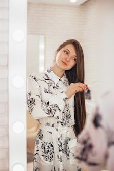 Молодая красивая женщина с длинными здоровыми волосами брюнетки смотрит в зеркало и расчесывает волосы