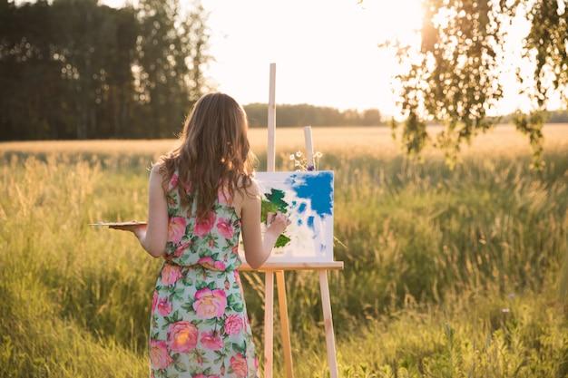 長い自然な髪の若い美しい女性が絵を描く