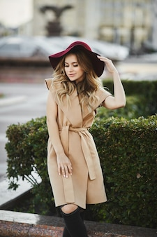 Молодая красивая женщина с длинными платиновыми светлыми волосами и ярким макияжем в модном весеннем наряде.