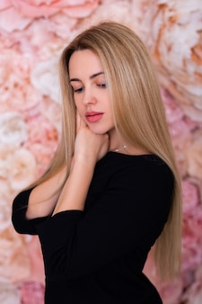 Young beautiful woman with long straight hair on flower wall background