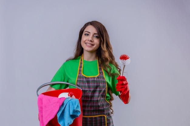 長いウェーブのかかった髪のエプロンと手袋のバケツを洗浄ツールとスクラブブラシのフレンドリーな立っている笑顔で保持している若い美しい女性