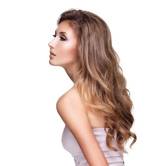 長いウェーブのかかった髪のポーズで若い美しい女性。白で隔離