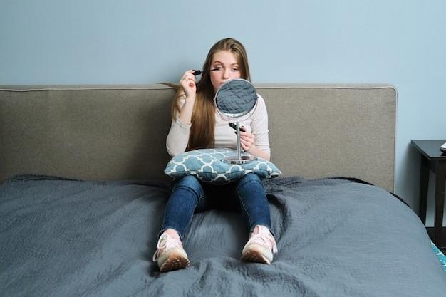 침대에서 집에 앉아있는 동안 메이크업 페인팅 마스카라 속눈썹을하고 메이크업 거울 장식 화장품을 가진 젊은 아름 다운 여자