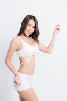 Young beautiful woman with measure tape.