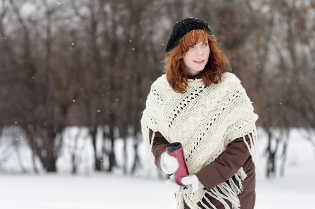 Young beautiful woman with metallic tumbler walking in winter park