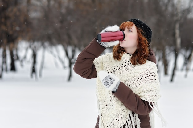 Young beautiful woman with metallic tumbler in winter park