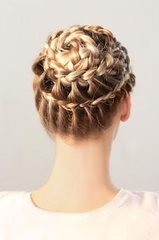 明るい背景に素敵な三つ編みの髪型を持つ若い美しい女性