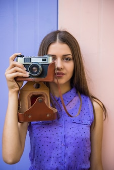 Young beautiful woman with old-fashioned camera.