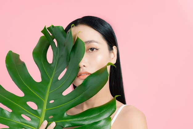 Young beautiful woman with a palm leaf on pink, clean skin. beauty concept
