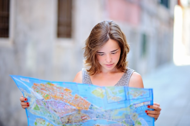 Young beautiful woman with paper map standing on street in venice, italy