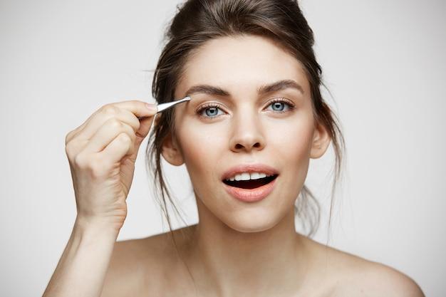 Молодая красивая женщина с идеально чистой кожей выщипывает брови. уход за лицом.
