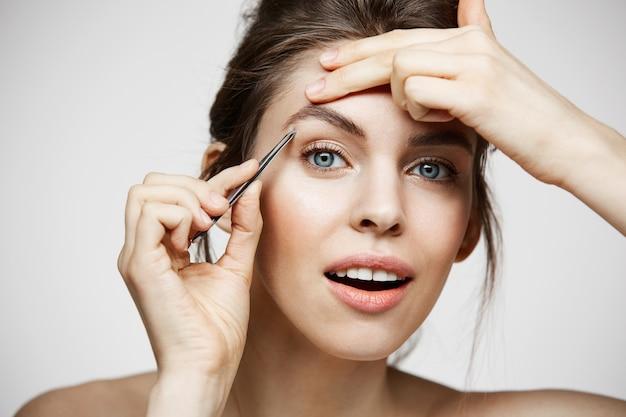 완벽 하 게 깨끗 한 피부를 가진 젊은 아름 다운 여자 눈 썹을 족 쇄. 페이셜 트리트먼트.