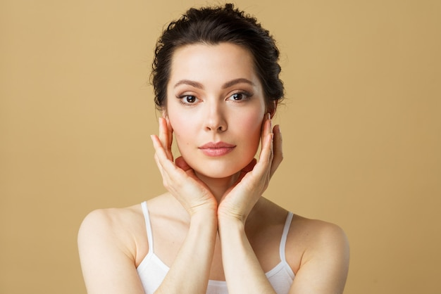 Young beautiful woman with perfect skin touching her face cosmetology beauty and spa concept female
