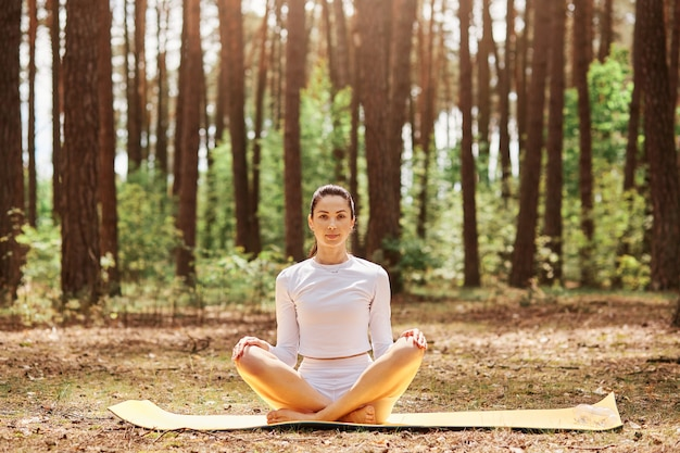 Young beautiful woman with pleasant appearance sitting on karemat in yoga pose