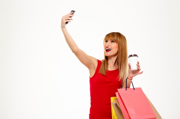 Young beautiful woman with purchases making selfie over white wall