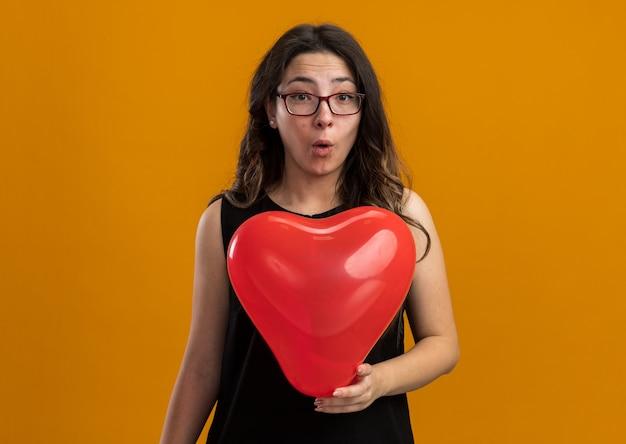 オレンジ色の壁越しにバレンタインデーを祝う驚いたように見える赤い風船を持つ若い美しい女性