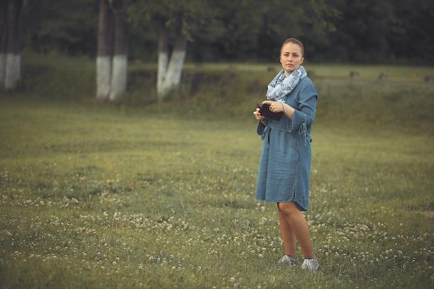 公園の芝生の上に立っている赤い髪とデニムのドレスを持つ若い美しい女性