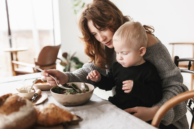 Young beautiful woman with red hair in knitted sweater sitting at the table dreamily feeding her little son