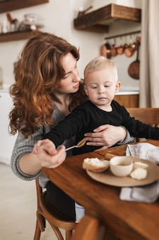 Young beautiful woman with red hair in knitted sweater sitting at the table with food dreamily feeding her little handsome son