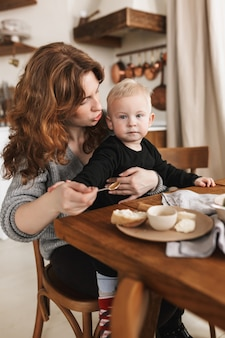 Young beautiful woman with red hair in knitted sweater sitting at the table with food dreamily feeding her little son