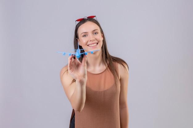 Giovane bella donna con occhiali da sole rossi sulla testa che tiene aeroplano giocattolo guardando la fotocamera sorridente con la faccia felice in piedi su sfondo bianco
