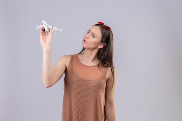 Giovane bella donna con gli occhiali da sole rossi sull'aeroplano del giocattolo della tenuta capa che sembra giocoso e felice sopra la parete bianca