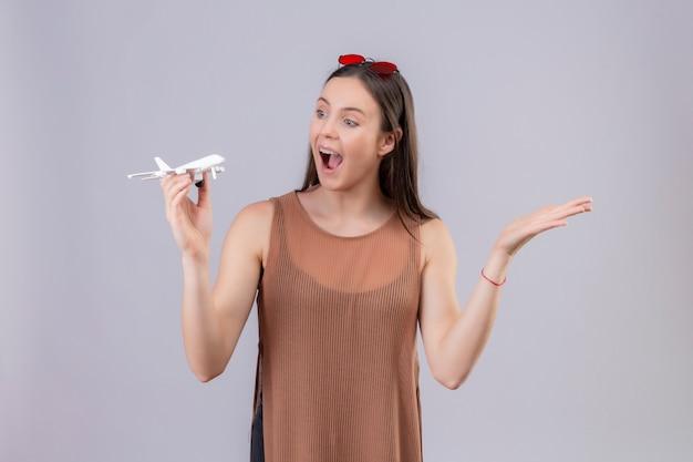 La giovane bella donna con gli occhiali da sole rossi sulla testa che tiene l'aeroplano del giocattolo che sembra allegra e felice con il braccio si è alzata sopra la parete bianca