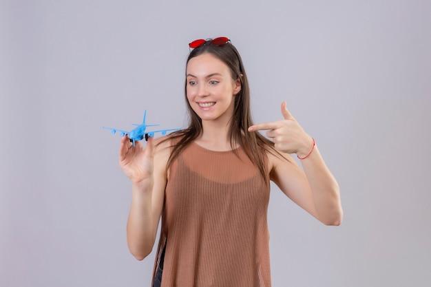 Giovane bella donna con occhiali da sole rossi sulla testa che tiene aeroplano giocattolo che punta con il dito ad esso sorridente positivo e felice in piedi su sfondo bianco