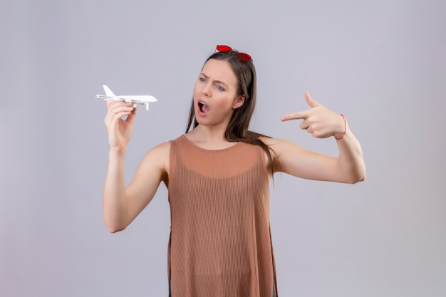 Giovane bella donna con occhiali da sole rossi sulla testa che tiene aeroplano giocattolo che punta con il dito ad esso sorpreso e stupito in piedi su sfondo bianco
