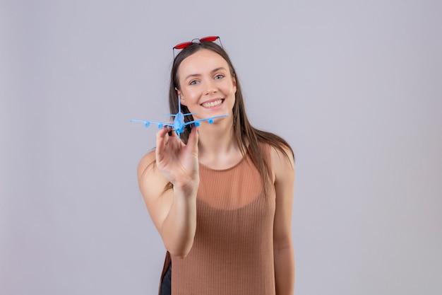 Giovane bella donna con gli occhiali da sole rossi sull'aeroplano capo del giocattolo della tenuta che sorride con il fronte felice sopra la parete bianca