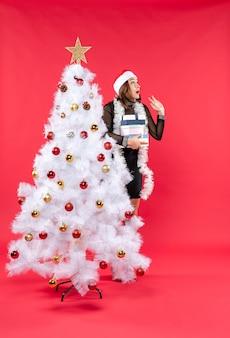 Молодая красивая женщина в шляпе санта-клауса стоит за украшенной елкой с подарками и смотрит вверх с удивлением