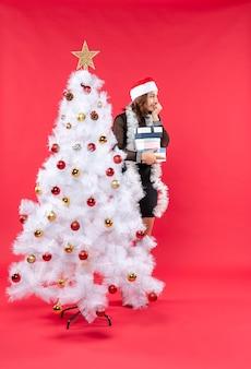 サンタクロースの帽子と飾られたクリスマスツリーの後ろに立って贈り物を保持し、幸せに何かを探している若い美しい女性