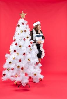 Молодая красивая женщина в шляпе санта-клауса стоит за украшенной елкой с подарками и смотрит что-то удивленное