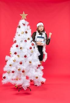 Молодая красивая женщина в шляпе санта-клауса стоит за украшенной елкой, держит подарки и смотрит
