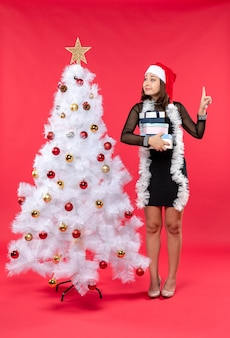 Young beautiful woman with santa claus hat and standing near the decorated christmas tree receiving her gifts and pointing above