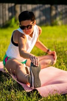 Молодая красивая женщина с короткими черными волосами растягивается на коврике для йоги на траве в парке, разминается перед тренировкой