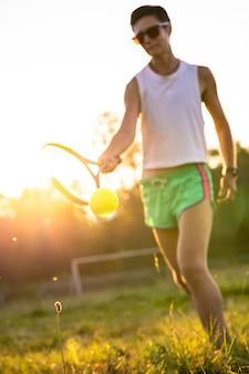 Молодая красивая женщина с короткими волосами играет в теннис на открытом воздухе