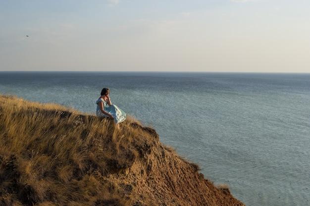 잔잔한 바다의 기슭에 일몰을보고 짧은 머리를 가진 젊은 아름 다운 여자.