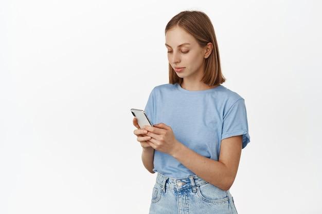 Giovane bella donna con i capelli corti scrivendo un messaggio sul cellulare. donna che guarda smartphone, sms o chat, scorrimento app social media, muro bianco.