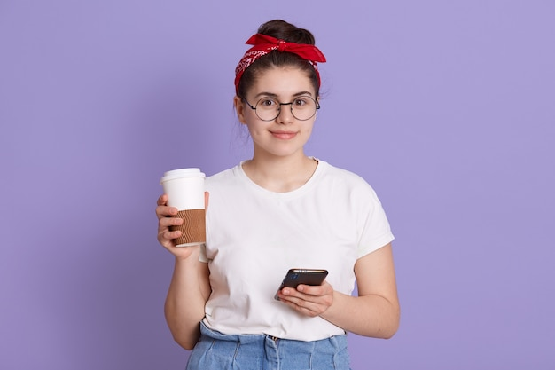 Young beautiful woman with smart phone and take away coffee, smiling student girl posing isolated over lilac space