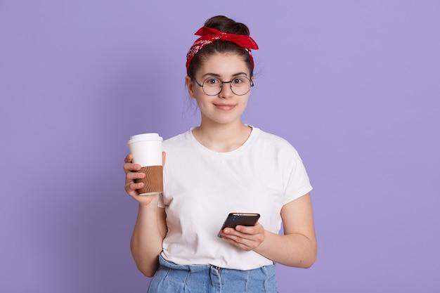 Giovane bella donna con smart phone e porta via il caffè, sorridente ragazza studentessa in posa isolato su spazio lilla