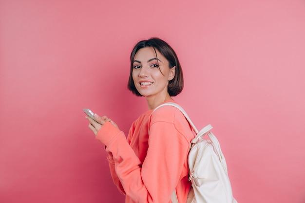 Giovane bella donna con lo smartphone. ragazza sorridente dell'allievo che va su un viaggio.