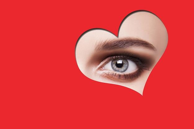 赤いハートの形を通してカメラを見ているスモーキーな目のメイクで若い美しい女性。赤い背景で隔離の屋内スタジオショット。