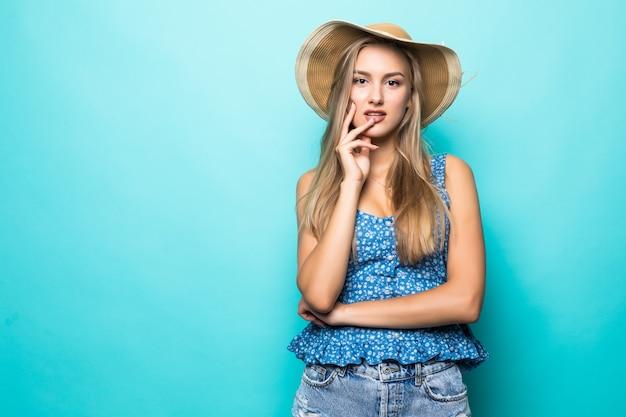 青い背景に笑顔で幸せな麦わら帽子と若い美しい女性